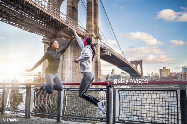 Athletes giving high-five against Brooklyn bridge