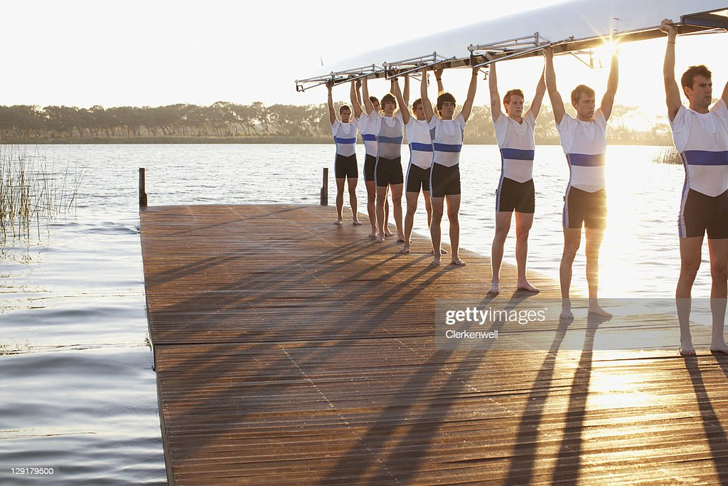 Athletes holding their boat upwards : Stock Photo