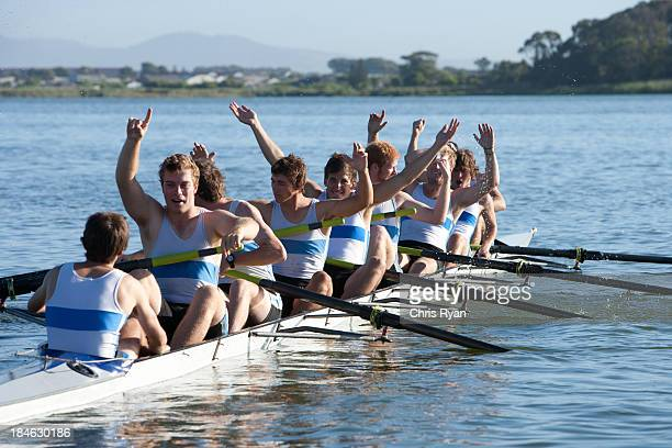 Athletes in a crew row boat cheering