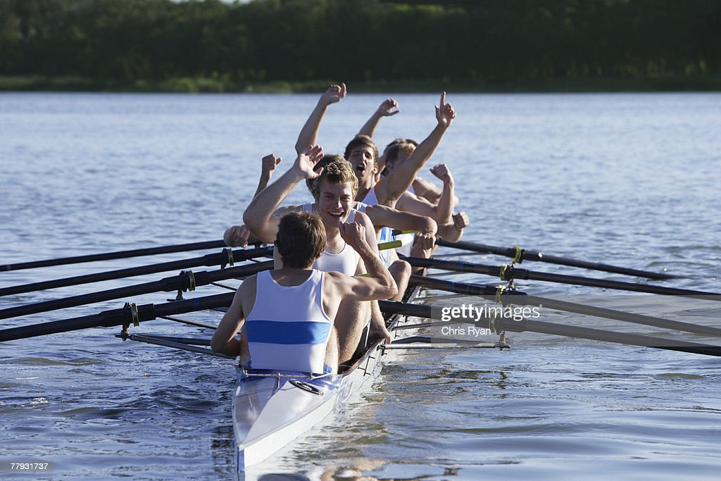 Athletes in a crew row boat cheering : Stock Photo