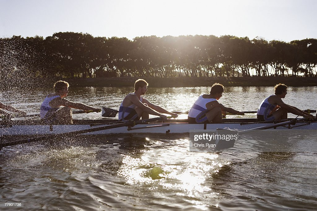 Athletes in a crew row boat midstroke : Stock Photo