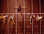 Athletes in race crossing finishing line, overhead view (Composite)