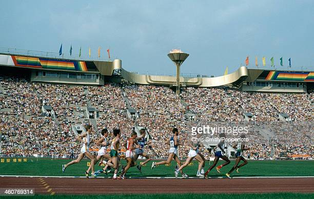 Athletes in the men's 5000 metres event run past the Olympic flame and cauldron during the Summer Olympic Games in Moscow circa July 1980