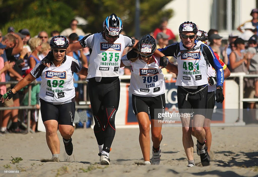 Athletes join togeather to cross the finish line during the 2013 Speights Coast to Coast on February 9, 2013 in Christchurch, New Zealand.