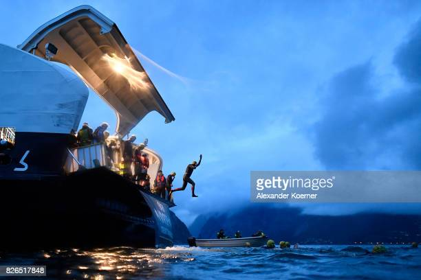 Athletes jump from a ferry into the Hardangerfjords as part of the swim leg during the start of the Isklar Norseman Extreme Triathlon August 5 2017...
