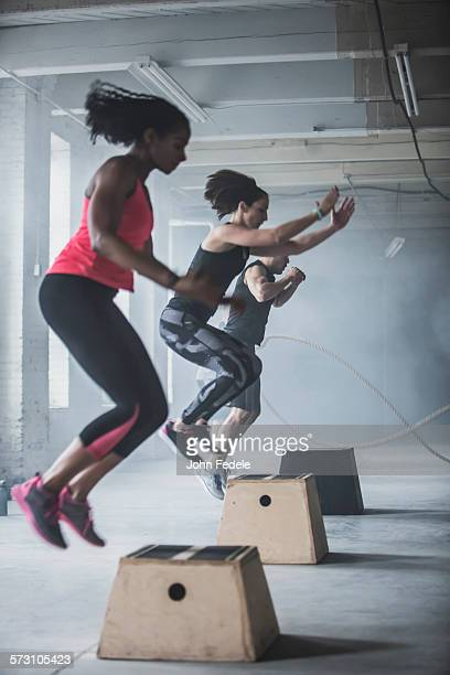 Athletes jumping on platforms in gym