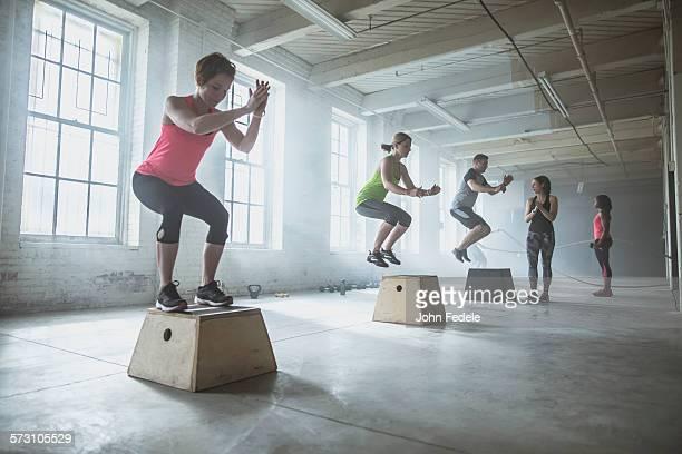 Athletes jumping on platforms in gym