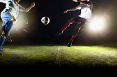 Athlete jumping towards soccer ball on field during game