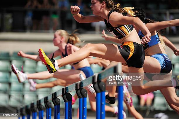 Athletes leap over hurdles while competing in the Womens Under 14's 80m Hurdle event during the Australian Junior Athletics Championships at Sydney...