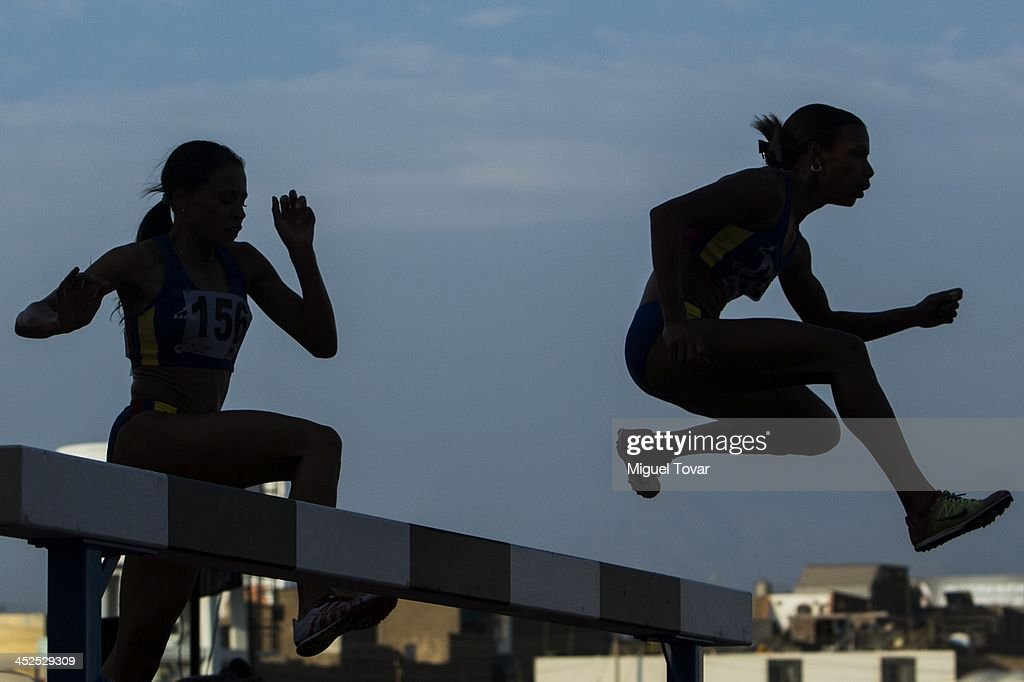 Athletes make their way over the water jump in women's 3,000m steeplechase final as part of the XVII Bolivarian Games Trujillo 2013 at Chan Chan Stadium on November 29, 2013 in Trujillo, Peru.