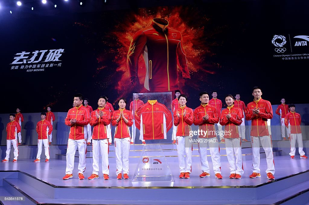 Athletes parade during a ceremony to unveil the Chinese Olympic team's uniforms for the Rio 2016 Olympic Games, in Beijing on June 29, 2016. The uniforms were unveiled at a ceremony in the Water Cube, the venue for the swimming competition at the 2008 Beijing Olympic Games. / AFP / WANG