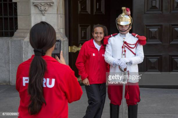 Athletes pose for photos alongside a gaurd of the palace after President of Peru Pedro Pablo Kuczynski received the Delegation of 33 Peruvian...