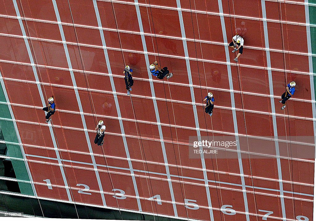 Athletes race the 100-meter track up the side of a skyscraper during the preliminary heats of the world's first track event in Hong Kong, 14 August 2004. The event dubbed 'Impossible is nothing' sponsored by one of the world's leading rubber shoes maker Adidas, tests the limits of athleticism and the challenges pre-conceived notions of the limits of the physical world. Around forty athletes joined the competition in Hong Kong which was simultaneoulsy held in Osaka Japan. Finals in Hong Kong will be held 22 August with the champion receiving 10, 000 USD prize.