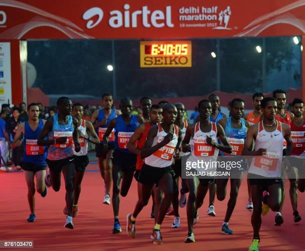Athletes run from the start line during the Airtel Delhi Half Marathon 2017 in New Delhi on November 19 2017 In the mens' category of the race...