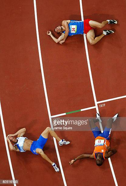 Athletes Slaven Dizdarevic of Slovakia Eugene Martineau of the Netherlands and Damjan Sitar of Slovenia lie exhausted on the track after crossing the...