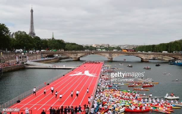 TOPSHOT Athletes take part in a race on a runway set near the Alexander III bridge on the Seine river in Paris on June 23 during an event to promote...