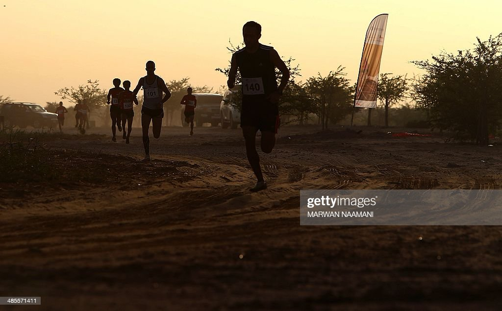 Athletes take part in the Dubai Desert Triathlon on April, 19, 2014 in the United Arab Emirate of Dubai. The event, a world first, brought together the heritage Emirati sport of endurance horse racing with the triathlon disciplines of running and cycling.