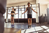 Muscular man and woman exercising using skipping rope in gym. Couple workout with jumping ropes in cross training gym.