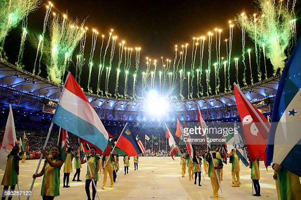 Athletes walk during the 'Heroes of the Games' segment as fireworks explode during the Closing Ceremony on Day 16 of the Rio 2016 Olympic Games at...