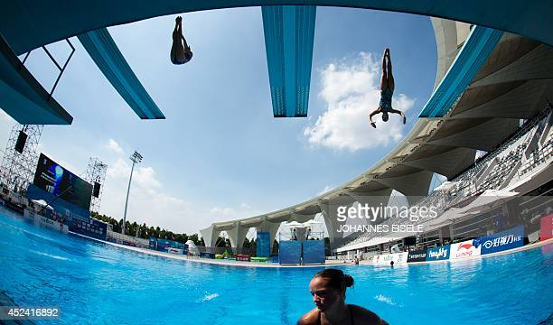 Athletes warm up during the women's three metre springboard final at the 19th FINA Diving World Cup in Shanghai on July 20 2014 AFP PHOTO / JOHANNES...