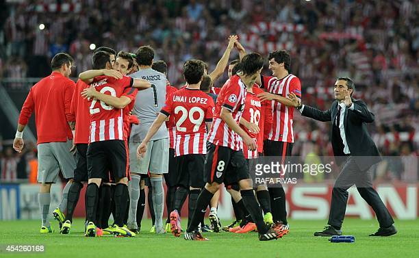 Athletic Bilbao's coach Ernesto Valverde celebrates with his players after winning the UEFA Champions League playoff second leg football match...