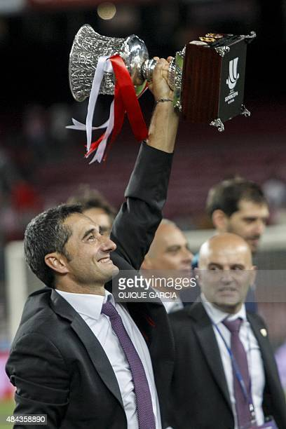 Athletic Bilbao's coach Ernesto Valverde raises the Supercup trophy as he celebrates after the Spanish Supercup secondleg football match FC Barcelona...