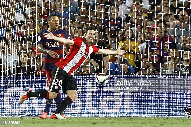 Athletic Bilbao's forward Aritz Aduriz celebrates after scoring a goal next to Barcelona's defender from Brazil Dani Alves during the Spanish...