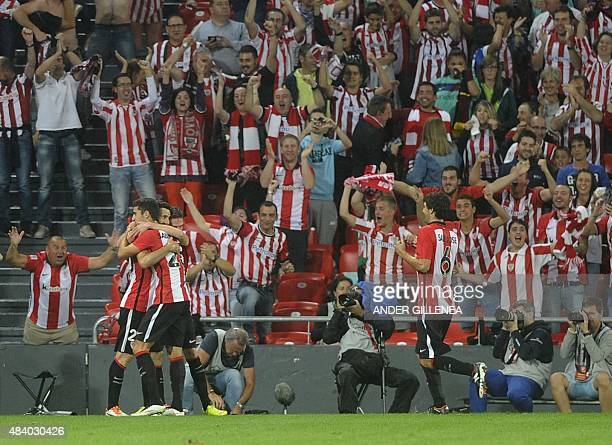 Athletic Bilbao's forward Aritz Aduriz is congratulated by teammates after scoring their team's fourth goal during the Spanish Supercup firstleg...