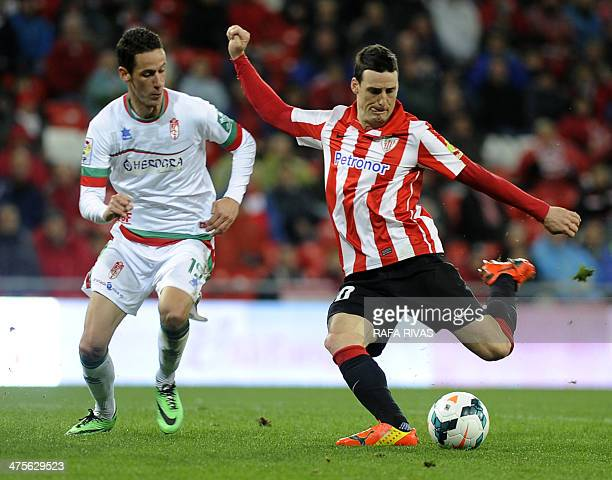 Athletic Bilbao's forward Aritz Aduriz shoots past Granada's French defender Alexandre Coeff during the Spanish league football match Athletic Club...
