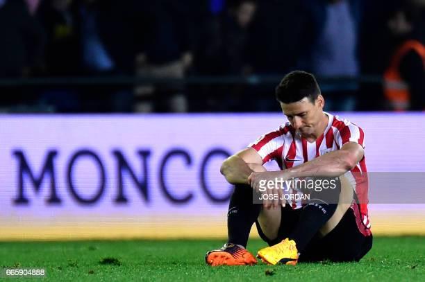Athletic Bilbao's forward Aritz Aduriz sits on the ground after the Spanish league football match Villarreal CF vs Athletic Club Bilbao at El...