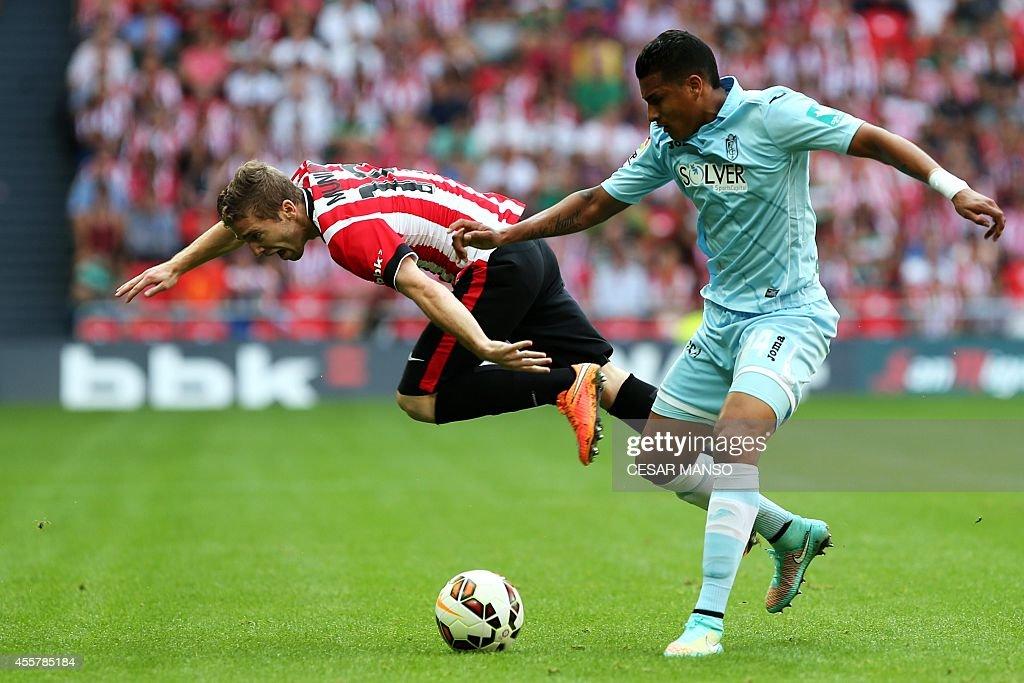 Athletic Bilbao's forward Muniain vies with Granada's Colombian forward Jeison Murillo during the Spanish league football match Athletic Club Bilbao...