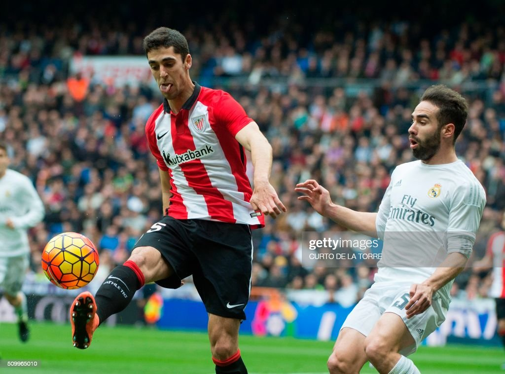 Athletic Bilbao's midfielder Javier Eraso Goni (L) vies with Real Madrid's defender Dani Carvajal during the Spanish league football match Real Madrid CF vs Athletic Club Bilbao at the Santiago Bernabeu stadium in Madrid on February 13, 2016. / AFP / CURTO DE LA TORRE