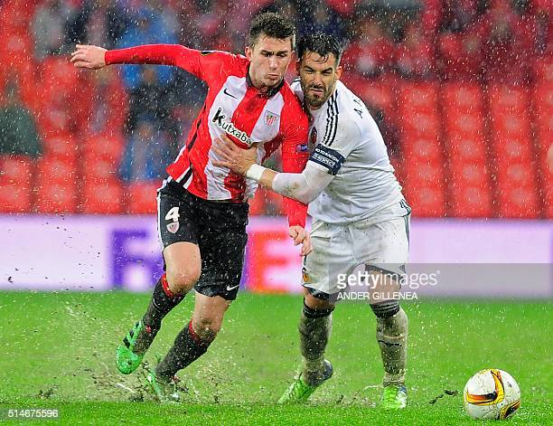 Athletic Bilbao's French defender Aymeric Laporte vies with Valencia's forward Alvaro Negredo during the UEFA Europa League Round of 16 first leg...