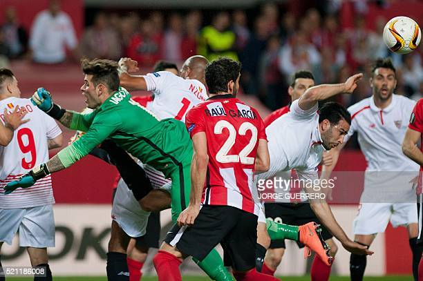 Athletic Bilbao's goalkeeper Iago Herrerin and midfielder Raul Garcia vie with Sevilla's French defender Adil Rami during the UEFA Europa League...