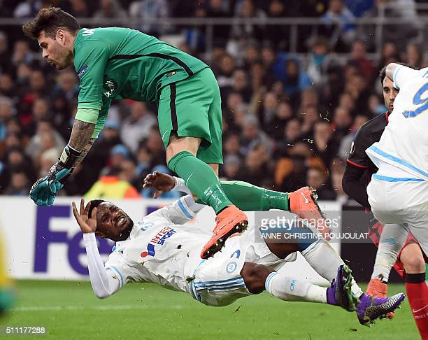 Athletic Bilbao's goalkeeper Iago Herrerin falls over Marseille's Cameroonian defender Nicolas Nkoulou during the UEFA Europa League round of 32...