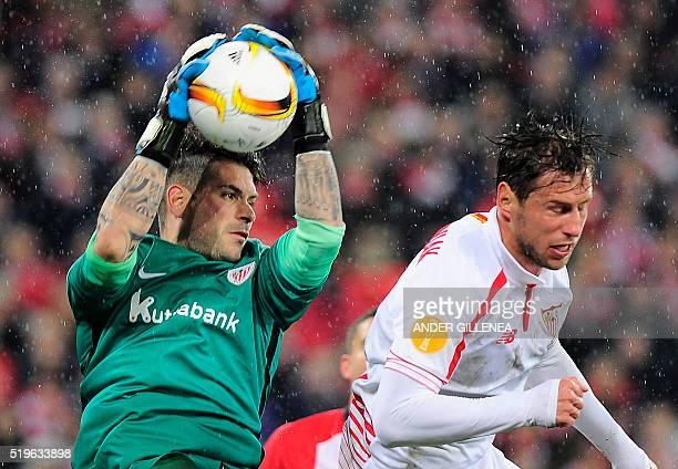 Athletic Bilbao's goalkeeper Iago Herrerin vies with Sevilla's Polish midfielder Grzegorz Krychowiak during the UEFA Europa League quarter finals...