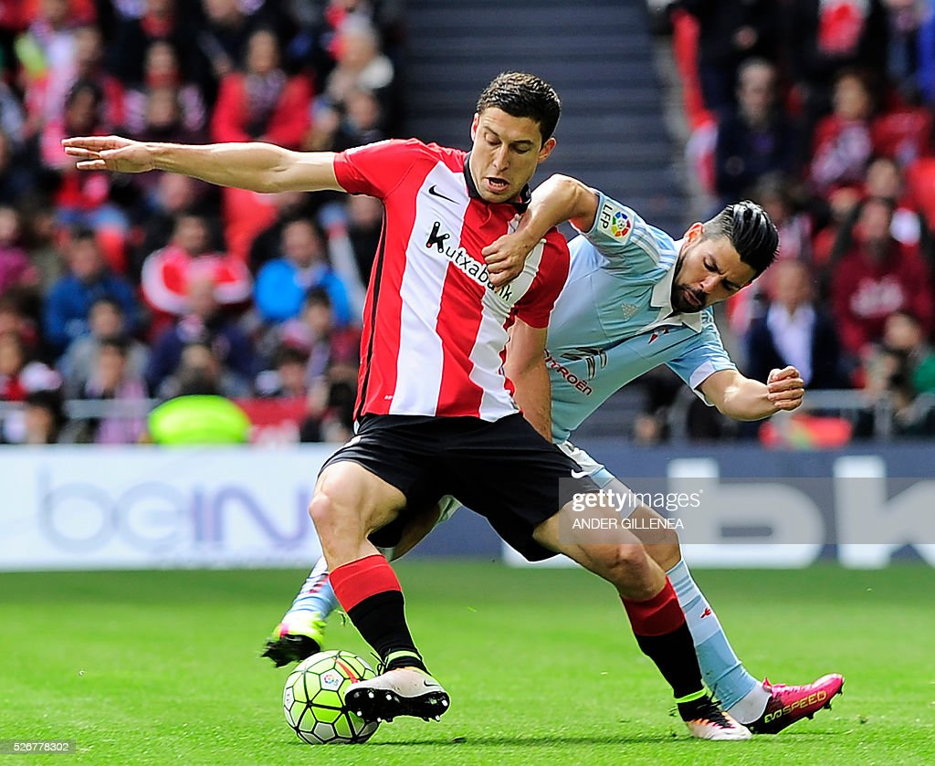 Athletic Bilbao's midfielder Oscar de Marcos (L) vies with Celta Vigo's forward Nolito during the Spanish league football match Athletic Club de Bilbao vs RC Celta de Vigo at the San Mames stadium in Bilbao on May 1, 2016. / AFP / ANDER