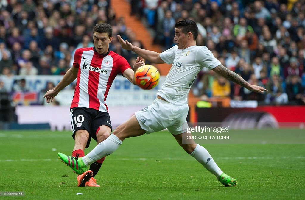Athletic Bilbao's midfielder Oscar De Marcos (L) vies with Real Madrid's Colombian midfielder James Rodriguez during the Spanish league football match Real Madrid CF vs Athletic Club Bilbao at the Santiago Bernabeu stadium in Madrid on February 13, 2016. / AFP / CURTO DE LA TORRE