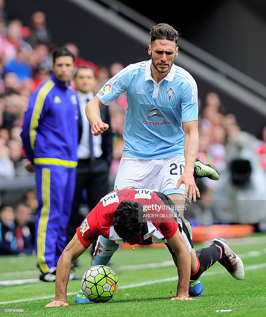 Athletic Bilbao's midfielder Raul Garcia (down) vies with Celta Vigo's defender Sergi Gomez during the Spanish league football match Athletic Club de Bilbao vs RC Celta de Vigo at the San Mames stadium in Bilbao on May 1, 2016. / AFP / ANDER