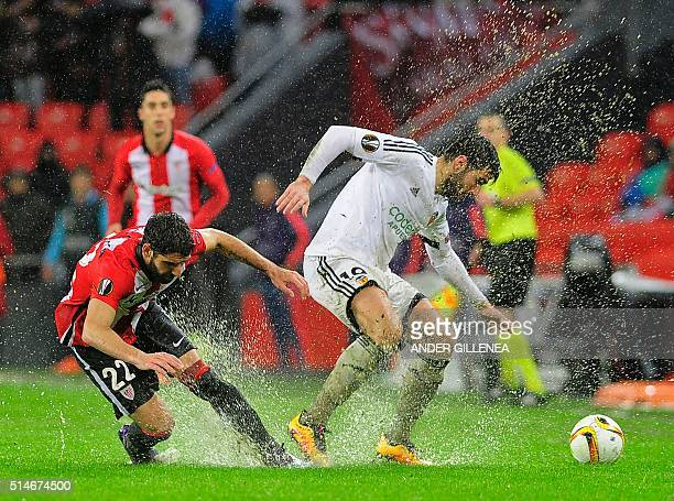 Athletic Bilbao's midfielder Raul Garcia vies with Valencia's Argentinian midfielder Enzo Perez during the UEFA Europa League Round of 16 first leg...