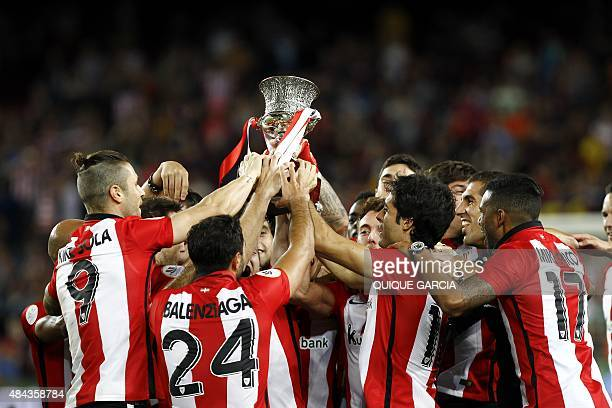 Athletic Bilbao's players hold the Supercup trophy after the Spanish Supercup secondleg football match FC Barcelona vs Athletic Club Bilbao at the...