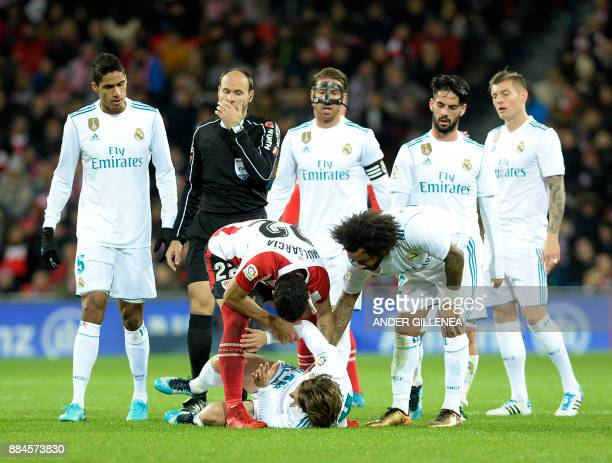 Athletic Bilbao's Raul Garcia Escuedro checks on Real Madrid's Croatian midfielder Luka Modric after a fall during the Spanish league football match...