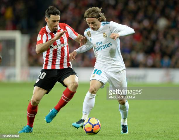 Athletic Bilbao's Spanish forward Aritz Aduriz challenges Real Madrid's Croatian midfielder Luka Modric during the Spanish league football match...