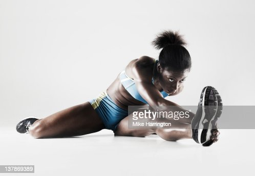 Athletic Black Female On Floor Stretching : Stock Photo