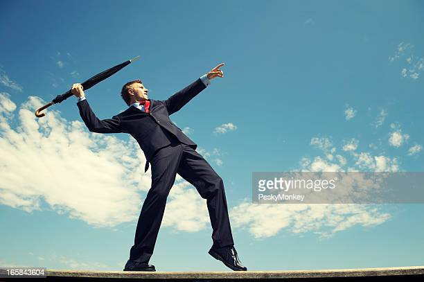 Athletic Businessman Standing Outdoors Throwing Javelin Umbrella Blue Sky
