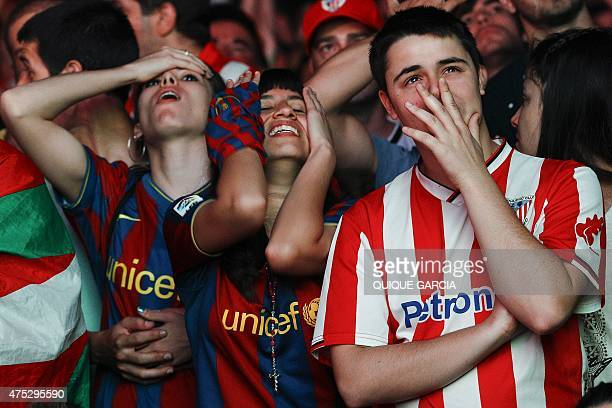 Athletic Club de Bilbao and FC Barcelona supporters react in the fanzone in Barcelona during the Spanish Copa del Rey final football match Athletic...