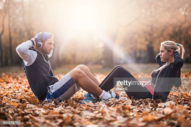 Athletic couple cooperating while doing sit-ups on autumn leaves.