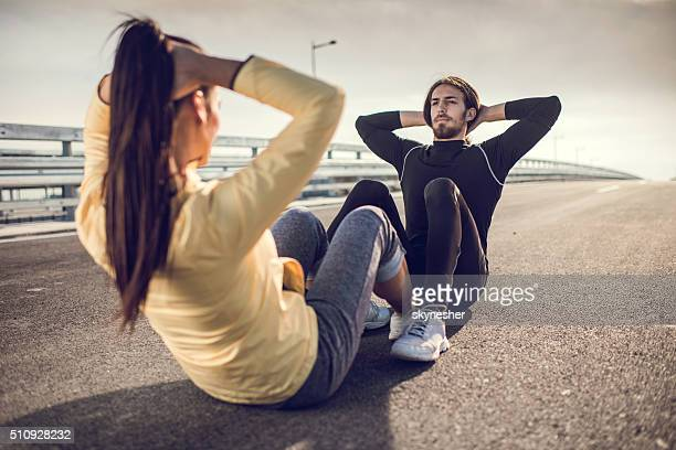 Athletic couple doing sit-ups on a road.