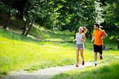 Athletic couple jogging in nature in good spirit