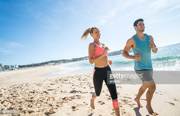 Athletic couple running at the beach